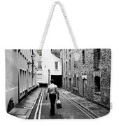 Man Walking With Shopping Bag Down Narrow English Street Weekender Tote Bag