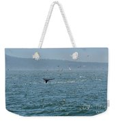 A Whale's Tail Above Water With Sail Boat In The Background Weekender Tote Bag