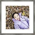Smiling Girl Lying On Autumn Leaves Framed Print