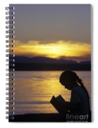Young Girl Silhouetted Reading A Book On The Beach At Sunset Spiral Notebook
