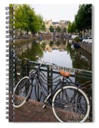 Bicycle Parked At The Bridge In Amsterdam. Netherlands. Europe Spiral Notebook