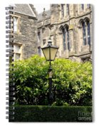 Lamppost In Front Of Green Bushes And Old Walls. Spiral Notebook