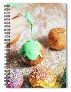 Woman's Hand Coating A Donut With Green Frosting. Spiral Notebook