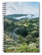 View Of Curved Road Through Dense Forest Area With Low Clouds Ov Spiral Notebook