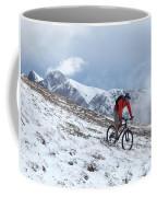 A Mountain Biker Rides Through The Snow Coffee Mug