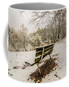 Park Bench In The Snow Covered Park Overlooking Lake Coffee Mug