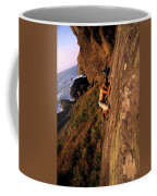 A Man Is Bouldering Near The Ocean Coffee Mug