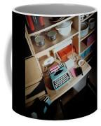 A Cupboard With A Blue Typewriter Coffee Mug