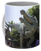 A Dinosaur Exhibit With Visitors In The Universal Studios Singapore Coffee Mug