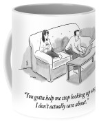 A Man And A Woman Sit On A Couch.  The Man Coffee Mug