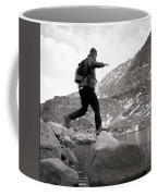A Man Jumps From One Rock To Another Coffee Mug