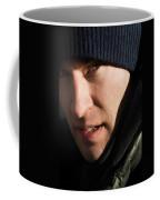 A Man Looks Up After Examining Coffee Mug