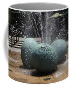 A Water Fountain With Dinosaur Eggs In The Universal Studios Singapore Coffee Mug