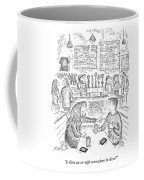A Woman And Man Sit At A Table And The Woman Coffee Mug