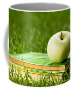 Apple On Pile Of Books On Grass Coffee Mug
