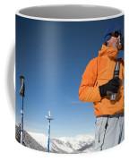Dressed In Orange, A Skier Sips A Warm Coffee Mug
