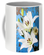 Lilies Against Blue Wall Coffee Mug