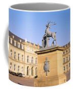 Low Angle View Of Statues In Front Of A Coffee Mug