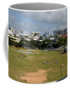 Schoolchildren Practicing On Playing Field With Singapore Skyline In Background Coffee Mug
