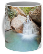 Small Waterfall Casdcading Over Rocks In Blue Pond Coffee Mug
