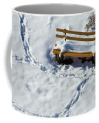 Snowy Foot Prints Around Snow Covered Park Bench Coffee Mug