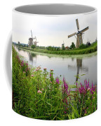 Windmills Of Kinderdijk With Wildflowers Coffee Mug by Carol Groenen