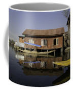 Yellow Shikara In Front Of A Run Down Area Of Houses In The Dal Lake Coffee Mug