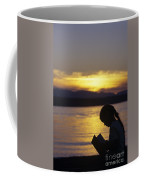 Young Girl Silhouetted Reading A Book On The Beach At Sunset Coffee Mug