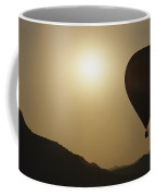 A Hot Air Balloon Rises Above A Hilly Coffee Mug