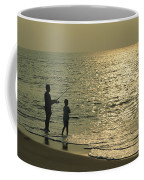 A Man And A Young Boy Fish In The Surf Coffee Mug