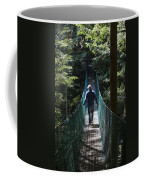 A Man Walks Across A Suspension Bridge Coffee Mug by Taylor S. Kennedy