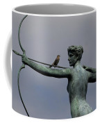 A Mockingbird Sits Atop A Bronze Coffee Mug