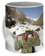 A Mujahadeen Guard Walks With U.s Coffee Mug