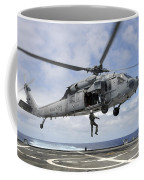 A Naval Aircrewman Is Hoisted Into An Coffee Mug