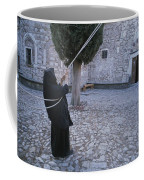 A Nun Pulls On Ropes In A Courtyard Coffee Mug by Tino Soriano