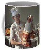 A Nurse Holds A Tightly Wrapped Newborn Coffee Mug by Dean Conger