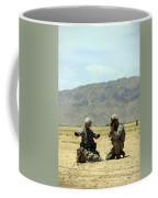 A Soldier Prepares A Drag Line While An Coffee Mug