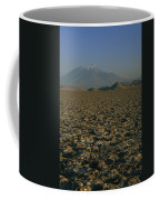 A Volcano Rises Above A Dry Lake Bed Coffee Mug