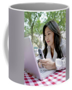 A Young Woman Checks Her Laptop Coffee Mug by Justin Guariglia