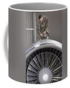 Airman Checks Components Atop A C-5 Coffee Mug