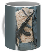 An Ak-47 Rests On The Sling Of An Coffee Mug