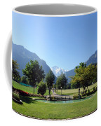 An Open Field In Interlaken With A View Of The Mountains In The Background Coffee Mug
