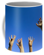 Childrens Hands Reach Toward The Blue Coffee Mug