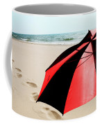 Red And Black Umbrella On The Beach With Footprints Coffee Mug