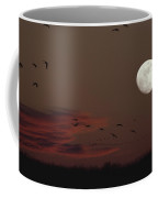 Silhouetted Sandhill Cranes Fly Near An Coffee Mug