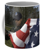 Soldier Unfurls A New Flag For Posting Coffee Mug by Stocktrek Images