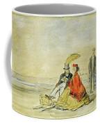 A Couple Seated And A Couple Walking On The Beach Coffee Mug