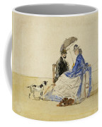 A Couple Seated On The Beach With Two Dogs Coffee Mug