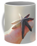 A Person Holds A Tiny Starfish Sea Star On Its Fingertip Of The Index Finger. Coffee Mug
