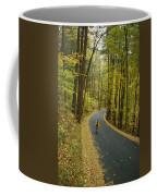 Biker On Road Amidst Fall Foliage Coffee Mug